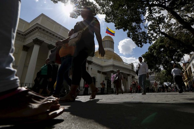 People walk past the National Assembly building during a session in Caracas December 10, 2015. REUTERS/Carlos Garcia Rawlins