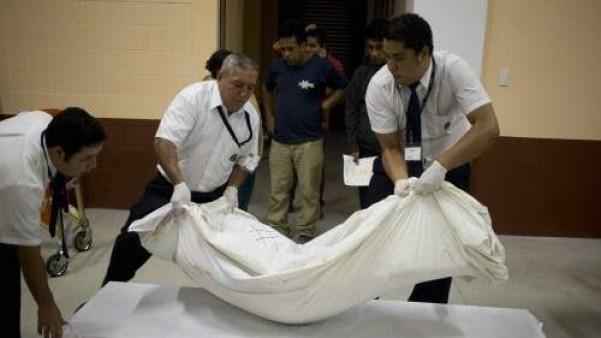 tres personas transportan un cadáver en una imagen de archivo