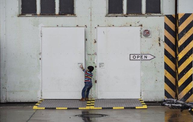 Un niño intenta abrir una puerta en un refigio de Berlín  AFP PHOTO / TOBIAS SCHWARZ