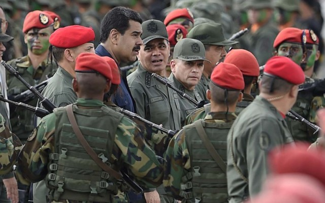 "Venezuelan President Nicolas Maduro (C-L) walks with Venezuelan Defense Minister Padrino Lopez (C-R) during a military parade in Caracas on December 12, 2015. Maduro asked Saturday the Armed Forces to get ready for an ""unconventional war"", as he promised job betterments for the military. AFP PHOTO/JUAN BARRETO / AFP / JUAN BARRETO"
