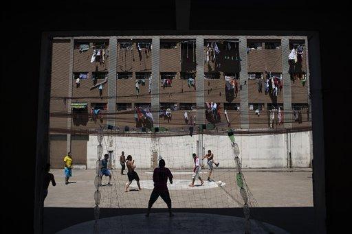 En esta imagen, tomada el 30 de noviembre de 2015, presos juegan al fútbol en la Prisión Central de Porto Alegre, Brasil, mientras las prendas de los internos cuelgan de las ventanas de sus celdas. Las instalaciones acogen al doble de reos de su capacidad, casi 2000 personas. (Foto AP/Felipe Dana)