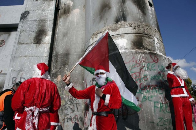 Palestinians dressed up as Santa Claus demonstrate in front of the Israeli controversial separation wall in the West Bank city of Bethlehem, on December 18, 2015.  AFP PHOTO / THOMAS COEX / AFP / THOMAS COEX