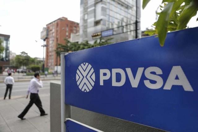 """Personas caminan cerca de un cartel de PDVSA, en una de sus gasolineras en Caracas, 28 de octubre de 2015. La estatal Petróleos de Venezuela (PDVSA) denunció el miércoles ser el centro de una """"campaña de desprestigio"""" internacional, luego que medios informaron que autoridades de Estados Unidos detectaron un supuesto esquema de sobornos por al menos 1.000 millones de dólares para ganar contratos de la firma. REUTERS/Marco Bello"""