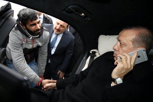 El presidente turco Recep Tayyip Erdogan, derecha, estrecha la mano de Vezir Cakras mientras habla por teléfono desde su auto detenido en el Puente del Bósforo en Estambul, 25 de diciembre de 2015. El presidente turco Recep Tayyip Erdogan convenció a un hombre que no saltara de un puente, informó su oficina el sábado 26 de diciembre de 2015. (Yasin Bulbul/Presidential Press Service Pool via AP Photo )