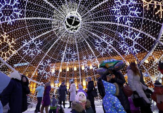 Varias personas caminan dentro de una gran bola decorativa de Navidad en la plaza Octyabrskaya durante las fiestas de Navidad y de Año Nuevo en Minsk (Bielorrusia) ayer, 29 de diciembre de 2015. EFE/Tatyana Zenkovich