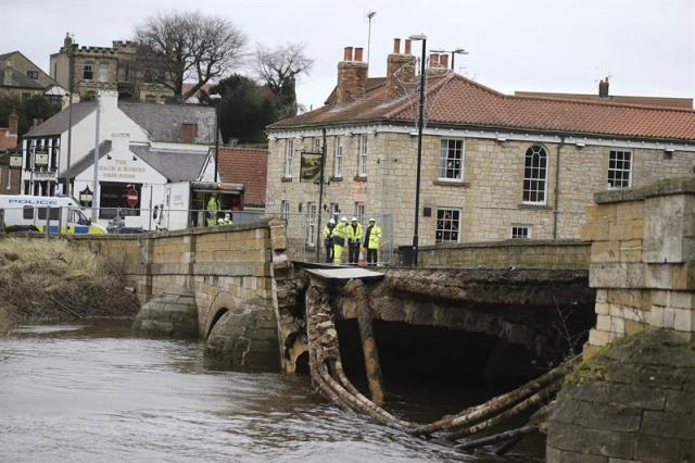 """Miembros de los servicios de emergencias permanecen junto a un puente que se ha hundido debido a las fuertes lluvias en Tadcastle en Yorkshire (Reino Unido) hoy, 30 de diciembre de 2015. Miles de hogares en Irlanda del Norte y Escocia han tenido problemas de suministro eléctrico debido a las fuertes lluvias y el viento provocados por la llegada hoy de """"Frank"""", un nuevo frente de tormenta procedente del Atlántico. EFE/Nigel Roddis"""