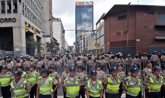 Venezuelan police officers, some in riot gear, line up in front of the the National Assembly in Caracas, on January 5, 2015. Venezuela's President Nicolas Maduro ordered the security forces to ensure the swearing-in of a new opposition-dominated legislature passes off peacefully Tuesday, after calls for rallies raised fears of unrest. AFP PHOTO/JUAN BARRETO / AFP / JUAN BARRETO