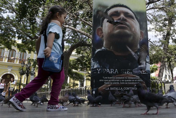 A girl runs among pigeons next to a portrait of Venezuela's late President Hugo Chavez at the Plaza Bolivar near the building housing the National Assembly in Caracas, January 8, 2016. REUTERS/Marco Bello