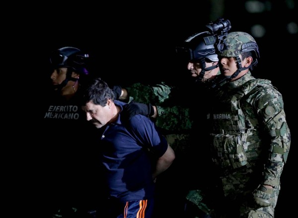 "Recaptured drug lord Joaquin ""El Chapo"" Guzman is escorted by soldiers at the hangar belonging to the office of the Attorney General in Mexico City, Mexico January 8, 2016.  REUTERS/Henry Romero"