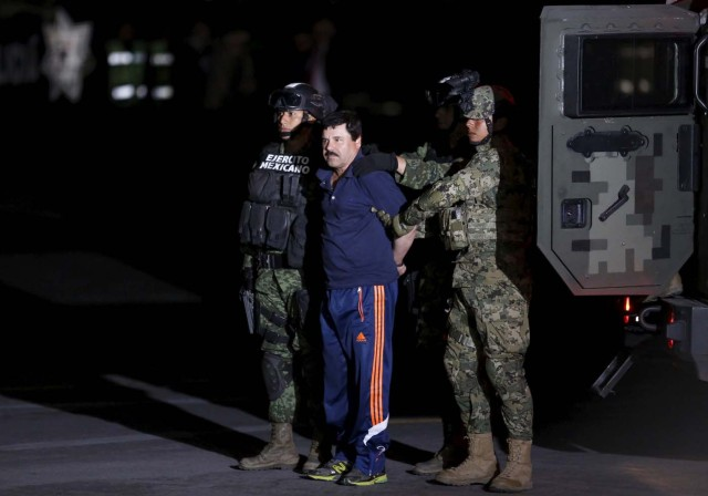 """Recaptured drug lord Joaquin """"El Chapo"""" Guzman is escorted by soldiers during a presentation in Mexico City, January 8, 2016.   REUTERS/Tomas Bravo"""