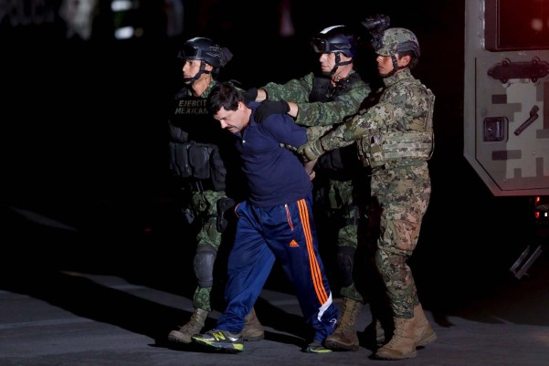 """Drug lord Joaquin """"El Chapo"""" Guzman is escorted by soldiers during a presentation in Mexico City, January 8, 2016. REUTERS/Tomas Bravo      TPX IMAGES OF THE DAY"""