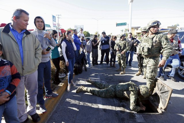 """A soldier tries pull out a weapon found in a drain from where Joaquin """"El Chapo"""" Guzman escaped before being captured at Jiquilpan Boulevard in Los Mochis, in Sinaloa state, Mexico, January 9, 2016. Mexico's government aims to fulfill a request from the United States to extradite the newly-recaptured drug lord Guzman to face drug trafficking charges, sources familiar with the situation said on Saturday. REUTERS/Edgard Garrido"""