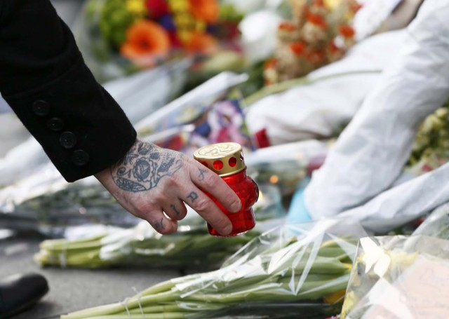 "A person places a candle next to tributes left next to a mural of David Bowie in Brixton, south London, January 11, 2016. David Bowie, a music legend who used daringly androgynous displays of sexuality and glittering costumes to frame legendary rock hits ""Ziggy Stardust"" and ""Space Oddity"", has died of cancer.  REUTERS/Stefan Wermuth"