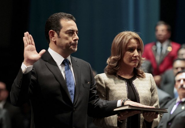 Jimmy Morales, accompanied by his wife Gilda Marroquin, takes the oath during his swearing-in ceremony as new president of Guatemala in Guatemala City, January 14, 2016. REUTERS/Jose Cabezas