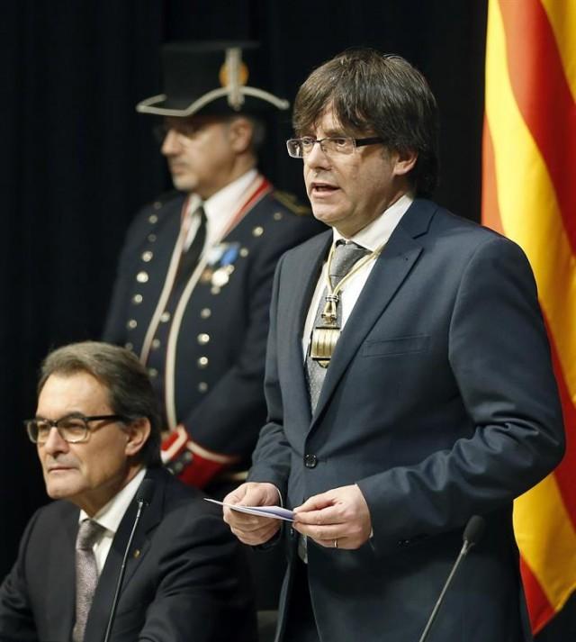 El nuevo presidente catalán, el independentista Carles Puigdemont, junto al expresidente Artur Mas (i), durante su discurso en el acto de toma de posesión que se ha celebrado hoy en el Palau de la Generalitat. EFE