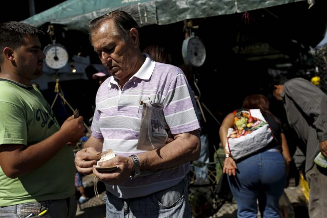 "A man counts bolivar notes to pay for his goods, at a vegetable street market in Caracas January 16, 2016. Venezuela's socialist government decreed an ""economic emergency"" on Friday that will expand its powers and published the first data in a year that shows the depth of a recession fueled by low oil prices and a sputtering state-led model. The central bank, which has been lambasted by critics of President Nicolas Maduro's government for hiding statistics since the end of 2014, said the South American OPEC nation's economy shrank 4.5 percent in the first nine months last year. Inflation soared in that period to an annual rate of 141.5 percent, the world's worst. REUTERS/Carlos Garcia Rawlins"