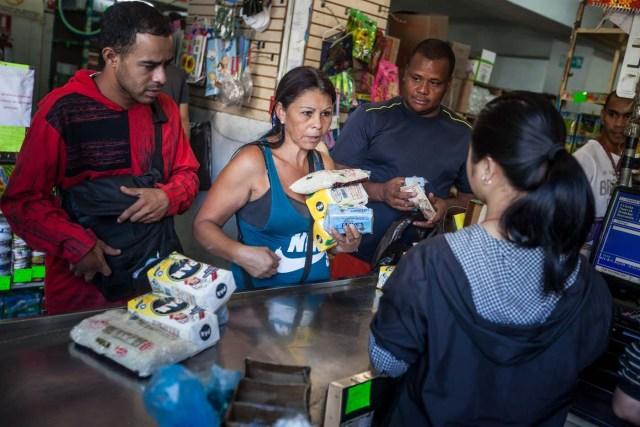 CAR01. CARACAS (VENEZUELA), 16/01/2016.- Clientes hacen fila para pagar productos que compraron en un abasto hoy, sábado 16 de enero de 2016, en la ciudad de Caracas (Venezuela). Venezuela, con las mayores reservas probadas de petróleo del mundo, se declaró en emergencia económica para atender la situación del país que después de un año de opacidad reveló una inflación interanual de 141,5 por ciento -la más alta de toda su historia-, y una contracción del 4,5 por ciento. EFE/MIGUEL GUTIÉRREZ