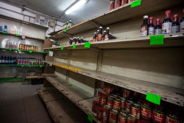 CAR01. CARACAS (VENEZUELA), 16/01/2016.- Vista de unos estantes parcialmente vacíos en un abasto hoy, sábado 16 de enero de 2016, en la ciudad de Caracas (Venezuela). Venezuela, con las mayores reservas probadas de petróleo del mundo, se declaró en emergencia económica para atender la situación del país que después de un año de opacidad reveló una inflación interanual de 141,5 por ciento -la más alta de toda su historia-, y una contracción del 4,5 por ciento. EFE/MIGUEL GUTIÉRREZ