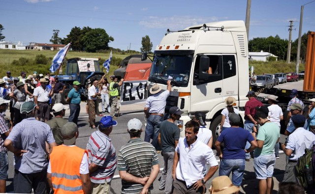 Productores lecheros bloquean una carretera principal contra los aumentos de precios en los servicios públicos y exigiendo el pago de unos 100 millones de dólares que Venezuela adeduda al sector en Libertad, Uruguay, el martes 19 de enero de 2016. (AP Foto/Matilde Campodonico)