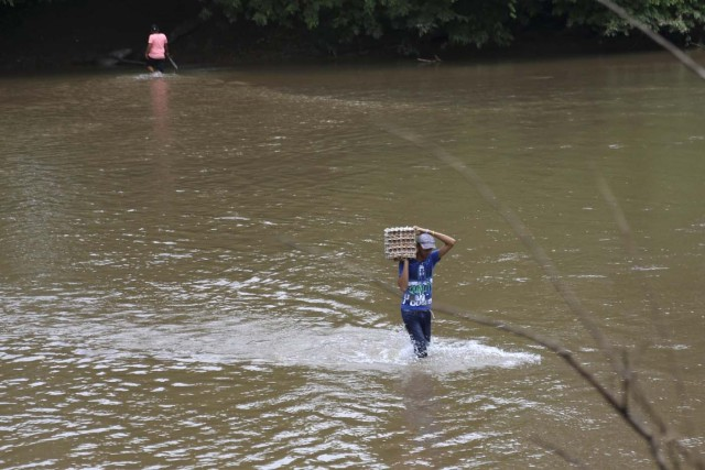 A man carries a carton of eggs across a river in the border town of Boca del Grita in the state of Tachira, Venezuela September 8, 2015. Driven by a deepening economic crisis, smuggling across Venezuela's land and maritime borders - as well as illicit domestic trading - has accelerated to unprecedented levels and is transforming society. Although smuggling has a centuries-old history here, the socialist government's generous subsidies and a currency collapse have given it a dramatic new impetus. To match Insight VENEZUELA-SMUGGLING/  Picture taken September 8, 2015. REUTERS/Girish Gupta
