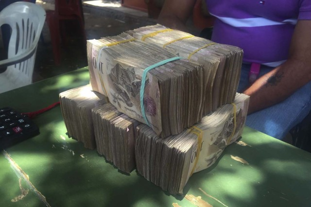 Venezuela's local currency lies on a currency trader's table in the border town of Maicao, Colombia August 18, 2015. Driven by a deepening economic crisis, smuggling across Venezuela's land and maritime borders - as well as illicit domestic trading - has accelerated to unprecedented levels and is transforming society. Although smuggling has a centuries-old history here, the socialist government's generous subsidies and a currency collapse have given it a dramatic new impetus. To match Insight VENEZUELA-SMUGGLING/ Picture taken August 18, 2015. REUTERS/Girish Gupta