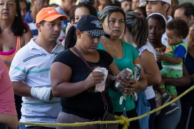 """CAR01. CARACAS (VENEZUELA), 23/01/2016.- Una mujer cuenta dinero mientras hace fila para comprar una bolsa con alimentos en una venta realizada en un edificio del plan habitacional gubernamental """"Misión Vivienda"""" hoy, sábado 23 de enero de 2016, en la ciudad de Caracas (Venezuela). El presidente del Parlamento venezolano, el opositor Henry Ramos Allup, reiteró hoy que los problemas que afronta su país con una aguda crisis económica de carestía y escasez se agravarán si Nicolás Maduro sigue en la jefatura del Estado. La situación económica del quinto productor de petróleo del mundo se ha visto golpeada por la caída de los precios del crudo, que inició en septiembre de 2014 cuando se cotizaba en 90 dólares por barril y que cerró esta semana en 21,63 dólares. """"Este Gobierno va a resolver nada; mientras esté allí todos los problemas de Venezuela van a empeorar totalmente. Hasta que no salgamos democráticamente de este Gobierno, Venezuela no se va a recuperar ni podrá resolver ninguno de sus problemas"""", subrayó en un discurso ante manifestantes antigubernamentales en Caracas. EFE/MIGUEL GUTIERREZ"""