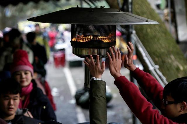 Varios pasajeros se acercan a una estufa mientras esperan la llegada de su autobús en un parque de Taipei (Taiwán) hoy, 25 de enero de 2016. Una oleada de frío en Taiwán se ha cobrado más de 85 vidas en la isla, en su mayoría de personas de más de 65 años y debido a problemas cardíacos y respiratorios desencadenados por las bajas temperaturas, según datos del Departamento de bomberos de la isla. EFE/Ritchie B. Tongo