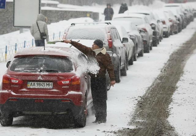 Un hombre limpia su coche después de una nevada en el centro de Kiev, Ucrania, 25 de enero de 2016. REUTERS / Gleb Garanich