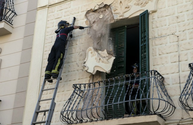 Bomberos eliminar una parte de una fachada dañada de un edificio en Melilla, España, después de un fuerte terremoto de magnitud 6,3 golpeó en la costa sur de España 25 de enero de 2016. REUTERS / Jesús Blasco de Avellaneda