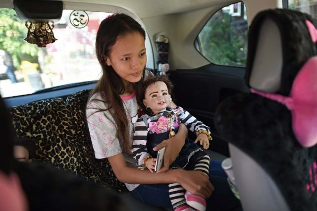 """TO GO WITH 'Thailand-lifestyle-society-religion' by Jerome TAYLOR This picture taken on January 28, 2016 shows a student and helper holding a """"luuk thep"""" (child angel) doll in a car on the way to a Buddhist temple outside the house of doll collector, producer and trader, Mananya Boonmee (not pictured) in Nonthaburi on the outskirts of Bangkok.  Seats at restaurant tables, in-flight meals, religious ceremonies and designer clothes are just some of the items Thais can buy their lucky """"angel dolls"""", the latest celebrity-fuelled supertitious craze that has swept the country much to the dismay of the kingdom's conservative military rulers.  AFP PHOTO / Christophe ARCHAMBAULT / AFP / CHRISTOPHE ARCHAMBAULT"""