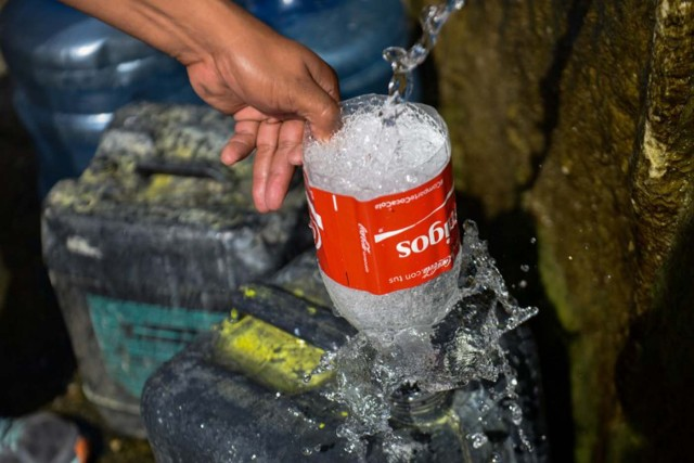 A man fills a jerry can with water from the Wuaraira Repano mountain in Caracas on January 21, 2016. Venezuela suffers a severe water shortage, which the government attributes to the delay in the arrival of the rainy season for the third consecutive year due to El Nino weather phenomenon. AFP PHOTO/FEDERICO PARRA / AFP / FEDERICO PARRA