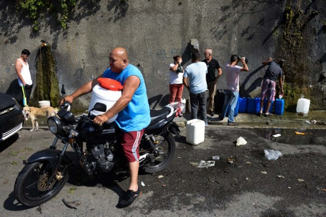 People line up to fill jerry cans with water from the Wuaraira Repano mountain in Caracas on January 21, 2016. Venezuela suffers a severe water shortage, which the government attributes to the delay in the arrival of the rainy season for the third consecutive year due to El Nino weather phenomenon. AFP PHOTO/FEDERICO PARRA / AFP / FEDERICO PARRA