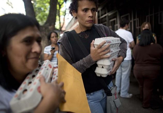 En esta imagen del miércoles 27 de enero de 2016, gente con cajas de huevos tras comprarlos a precios regulados por el gobierno en Caracas, Venezuela. Hay un desabastecimiento de huevos en el país. En una nota publicada el pasado viernes, el director del Fondo Monetario Internacional para el hemisferio oeste, Alejandro Werner, dijo que este año la inflación podría más que multiplicarse por dos en el país, hasta alcanzar el 720%. (AP Foto/Ariana Cubillos)