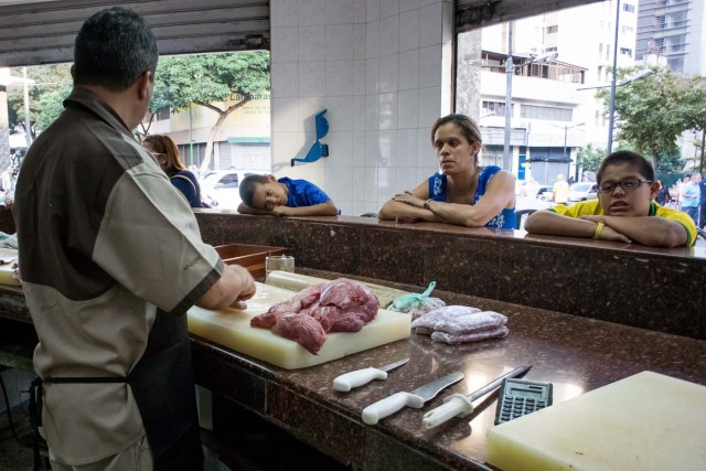 """CAR04. CARACAS (VENEZUELA), 11/02/2016.- Un carnicero atiende a sus clientes hoy, jueves 11 de febrero de 2016, en Caracas (Venezuela). El Parlamento venezolano declaró hoy la """"crisis alimentaria nacional"""" y en virtud de ello pidió que la FAO y la Unicef envíen expertos que evalúen los riesgos que entraña el problema para los 30 millones de habitantes del país caribeño. EFE/Miguel Gutiérrez"""