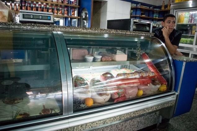 """CAR11. CARACAS (VENEZUELA), 11/02/2016.- Un joven espera los clientes en una tienda hoy, jueves 11 de febrero de 2016, en Caracas (Venezuela). El Parlamento venezolano declaró hoy la """"crisis alimentaria nacional"""" y en virtud de ello pidió que la FAO y la Unicef envíen expertos que evalúen los riesgos que entraña el problema para los 30 millones de habitantes del país caribeño. EFE/Miguel Gutiérrez"""