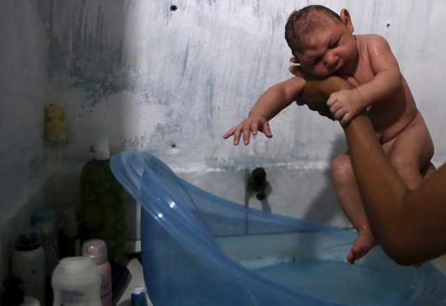 Daniele Santos, 29, holds her son Juan Pedro who is 2-months-old and born with microcephaly, after bathing him at their house in Recife, Brazil, February 9, 2016. The Zika virus may be particularly adept at entrenching itself in parts of the body that are shielded from the immune system, making it harder to fight off and possibly lengthening the timeframe in which it can be transmitted, top U.S. experts said on Friday. Picture taken February 9, 2016.  REUTERS/Nacho Doce