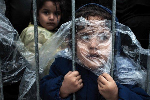 """Primer premio de la gategoría """"Gente"""", Matic Zorman. El niño se cubre con un impermeable mientras espera para registrarse en un campo de refugiados en Presevo, Serbia"""