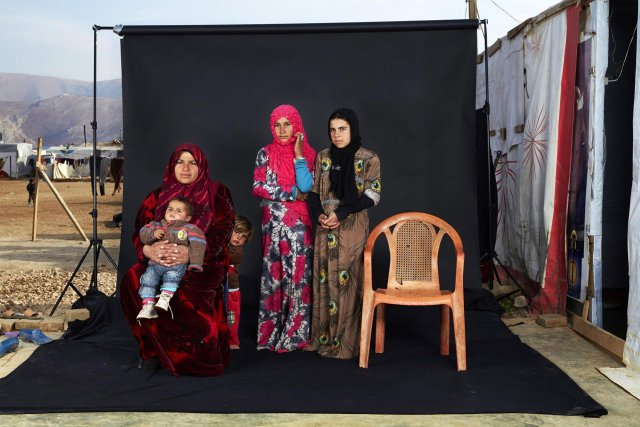 """Tercer premio de la categoría """"Gente"""", Dario Mitidieri. Retrato de una familia de refugiados sirios en un campamento en el valle de la Bekaa, Líbano. La silla vacía en la fotografía representa un miembro de la familia que ha ya sea muerto en la guerra o c"""