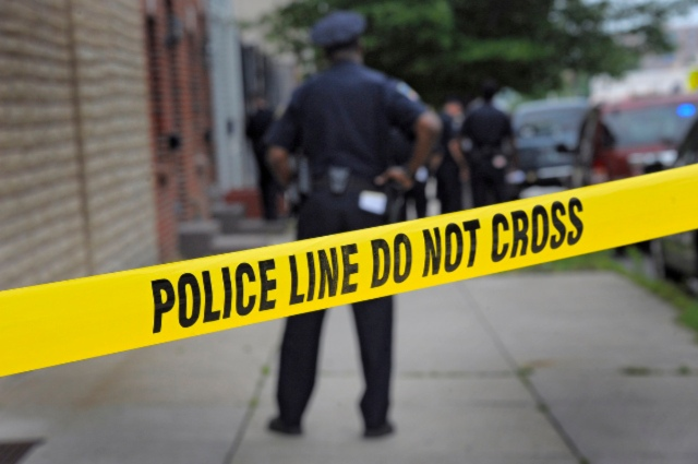 A Baltimore Police officer stands behind crime scene tape at the scene of a police-involved shooting following a dispatch for a burglary in progress, reported near S. Chester Street and Bank Street in southeast Baltimore. A suspect was shot, while another was taken into custody as investigators pore through evidence. (Karl Merton Ferron/Baltimore Sun)