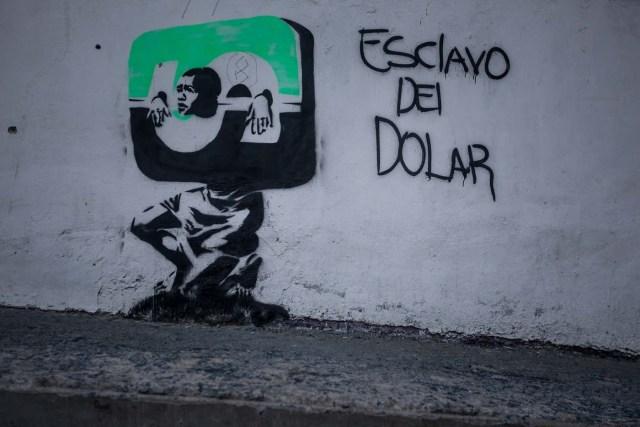 """CAR01. CARACAS (VENEZUELA), 09/03/2016.- Vista de un grafiti con la frase """"Esclavo del Dolar"""" hoy, miércoles 9 de marzo de 2016, en la ciudad de Caracas (Venezuela). El vicepresidente de Economía Productiva de Venezuela, Miguel Pérez Abad, anunció hoy que la tasa de cambio en divisas para los venezolanos que deseen viajar al exterior será más de un 1.500 por ciento superior a la que se aplicaba hasta ahora, de acuerdo a los ajustes del nuevo sistema cambiario. EFE/MIGUEL GUTIERREZ"""