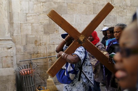 Worshippers carry a cross during a Good Friday procession through the Via Dolorosa in Jerusalem's Old City March 25, 2016. REUTERS/Ammar Awad