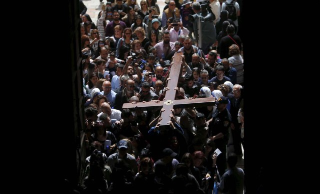 Worshippers carry a cross into the Church of the Holy Sepulcher during the Good Friday procession in Jerusalem's Old City March 25, 2016. REUTERS/Ammar Awad