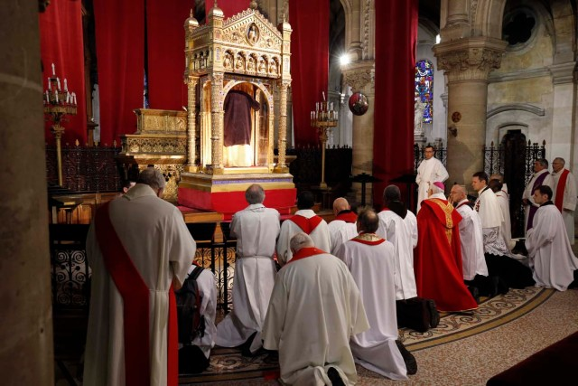 Communicants and priests pray in front of Christ's Holy Tunic during its rare exhibition in a large reliquary showcase at the Basilica of St. Denys of Argenteuil, near Paris, France, March 25, 2016. Christ's Holy Tunic is only on exhibit twice a century.  REUTERS/Philippe Wojazer