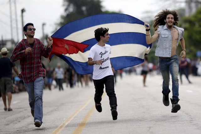 Fans run with a Cuban flag outside Ciudad Deportiva de la Habana sports complex where the Rolling Stones' free outdoor concert will take place today in Havana, March 25, 2016. REUTERS/Ueslei Marcelino