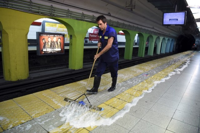 "Argentine writer Enrique ""Kike"" Ferrari mops the floor of a subway station in Buenos Aires, Argentina, on March 14, 2016. Ferrari is an award-winning writer who makes his living cleaning a metro station in Argentina. His noir novels were translated into four languages in six countries, and received awards in Spain and Cuba. AFP PHOTO/EITAN ABRAMOVICH / AFP / EITAN ABRAMOVICH"