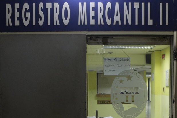 """A sign that reads """"Non-working day. Monday from 7:00am to 1:00pm"""", hangs at the door of a closed mercantile registry office in Caracas, April 8, 2016. REUTERS/Marco Bello"""