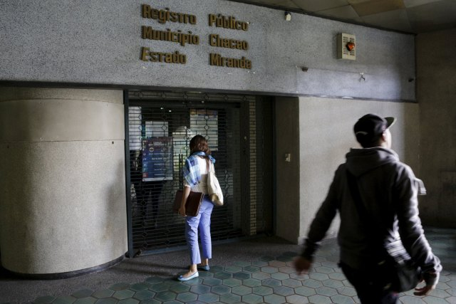A woman stands in front of a closed public registry office in Caracas, April 8, 2016. REUTERS/Marco Bello
