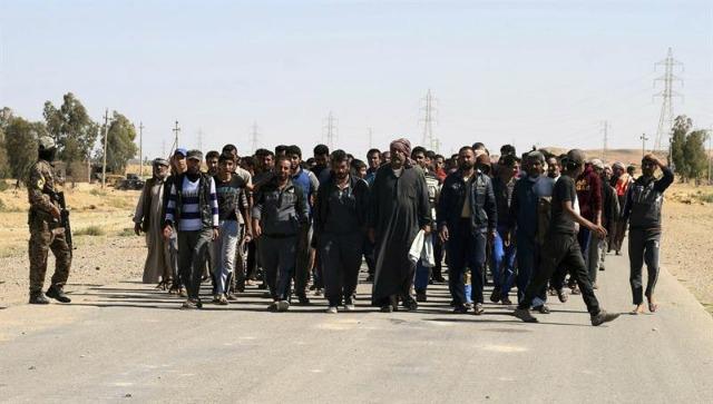 Fotografía que muestra a un soldado iraquí mientras escolta a docenas de hombres de la recién recuperado término municipal de la ciudad de Hit, a 60 kilómetros al oeste de Ramadi, en Irak, el 4 de abril de 2016. Al menos 24 combatientes del grupo Estado Islámico (EI) y cinco soldados murieron el pasado 3 de abril en la provincia occidental iraquí de Al Anbar en enfrentamientos entre yihadistas y el Ejército y en bombardeos de la coalición internacional liderada por EEUU. EFE/NAWRAS AAMER