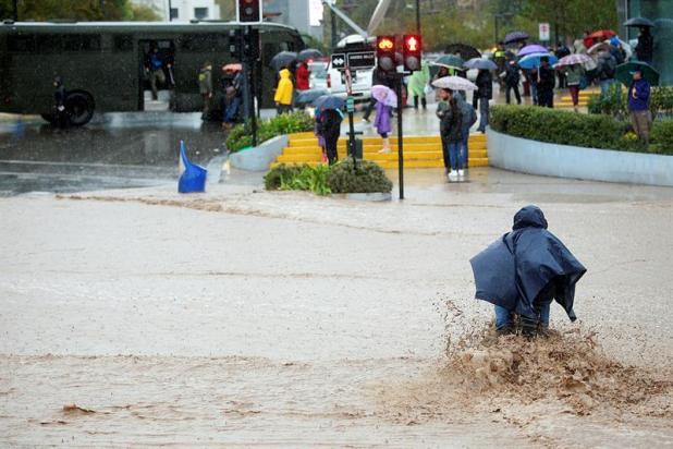 """Un hombre en bicicleta intenta cruzar una calle inundada hoy, domingo 17 de abril de 2016, debido a las lluvias en la región metropolitana, donde la autoridad ha decretado """"alerta roja"""", cuando más de cuatro millones de personas se encuentran sin suministro de agua potable, y cientos de calles se encuentran intransitables. Al menos un muerto, cinco desaparecidos, un millar de damnificados, crecidas de ríos y varios aludes es el saldo que ha dejado el temporal de viento y lluvia que afecta desde este sábado la zona central de Chile. EFE/Mario Ruiz"""