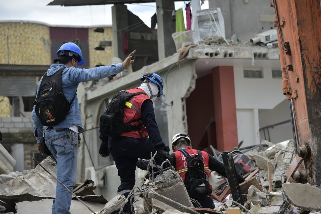 Rescue workers search the rubble in Pedernales, Ecuador on April 17, 2016 after a 7.8-magnitude quake hit the city the day before. At least 233 people have been killed in the 7.8-magnitude earthquake that struck Ecuador's Pacific coast, President Rafael Correa said Sunday. / AFP PHOTO / RODRIGO BUENDIA